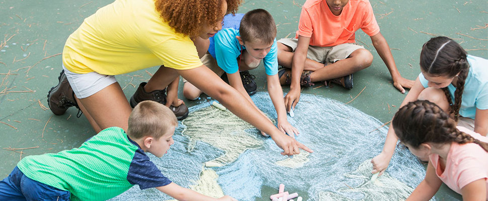 a group of children and a guardian making chalk art on a sidewalk