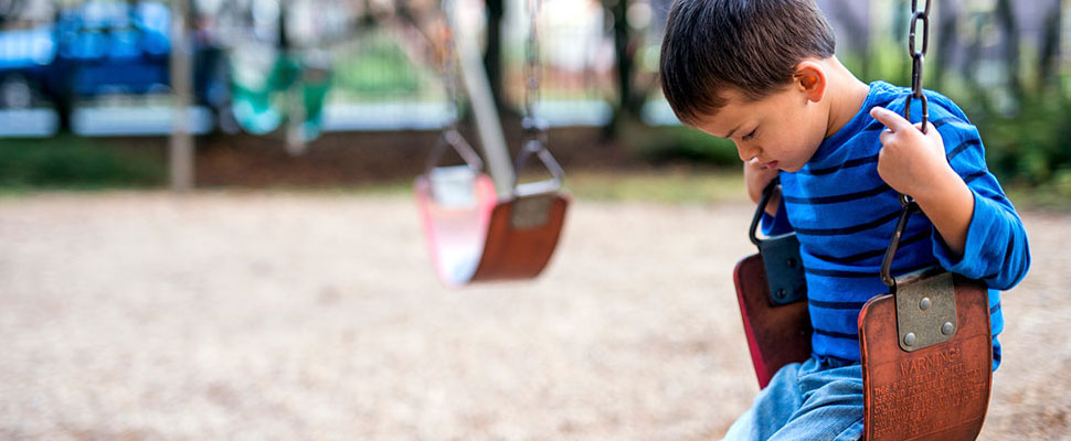image of a child looking sad on a swing