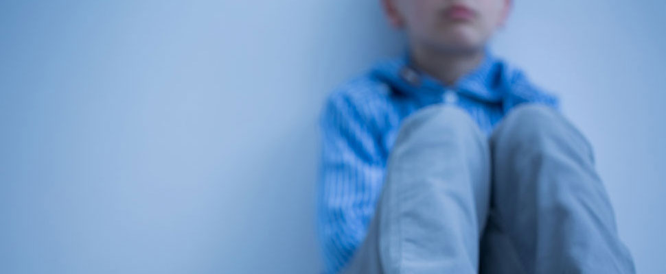 image of a boy sitting against a wall looking very sad